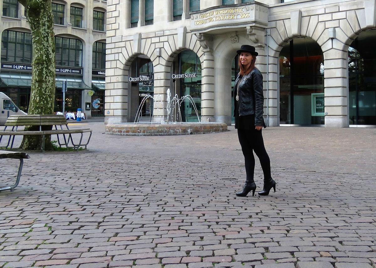 Schwarz: schwarzer Long Pullover mit Seitenschlitzen von Hallhuber-schwarze Leggings und Strumpfhose von Kalke- schwarzer Porkpie-Hut aus London- schwarze Ankle Boots von Paul Green- schwarze Lederjacke von Only
