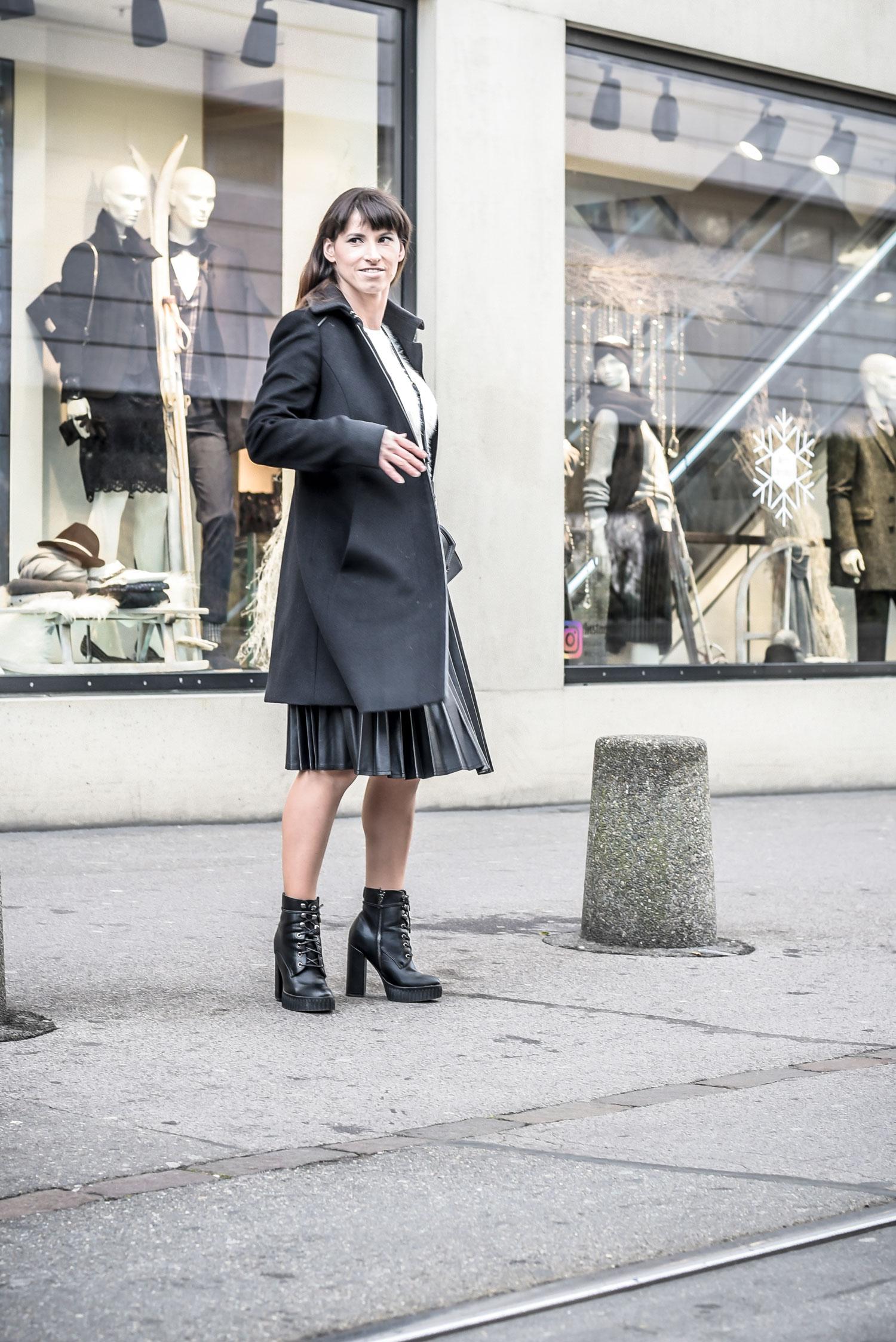 Plisseerock: Plisseerock aus Lederimitat von Reserved, weisser kuschelpullover von Guess, schwarze Stiefeletten von Guess, Camera-Bag von Karl Lagerfeld